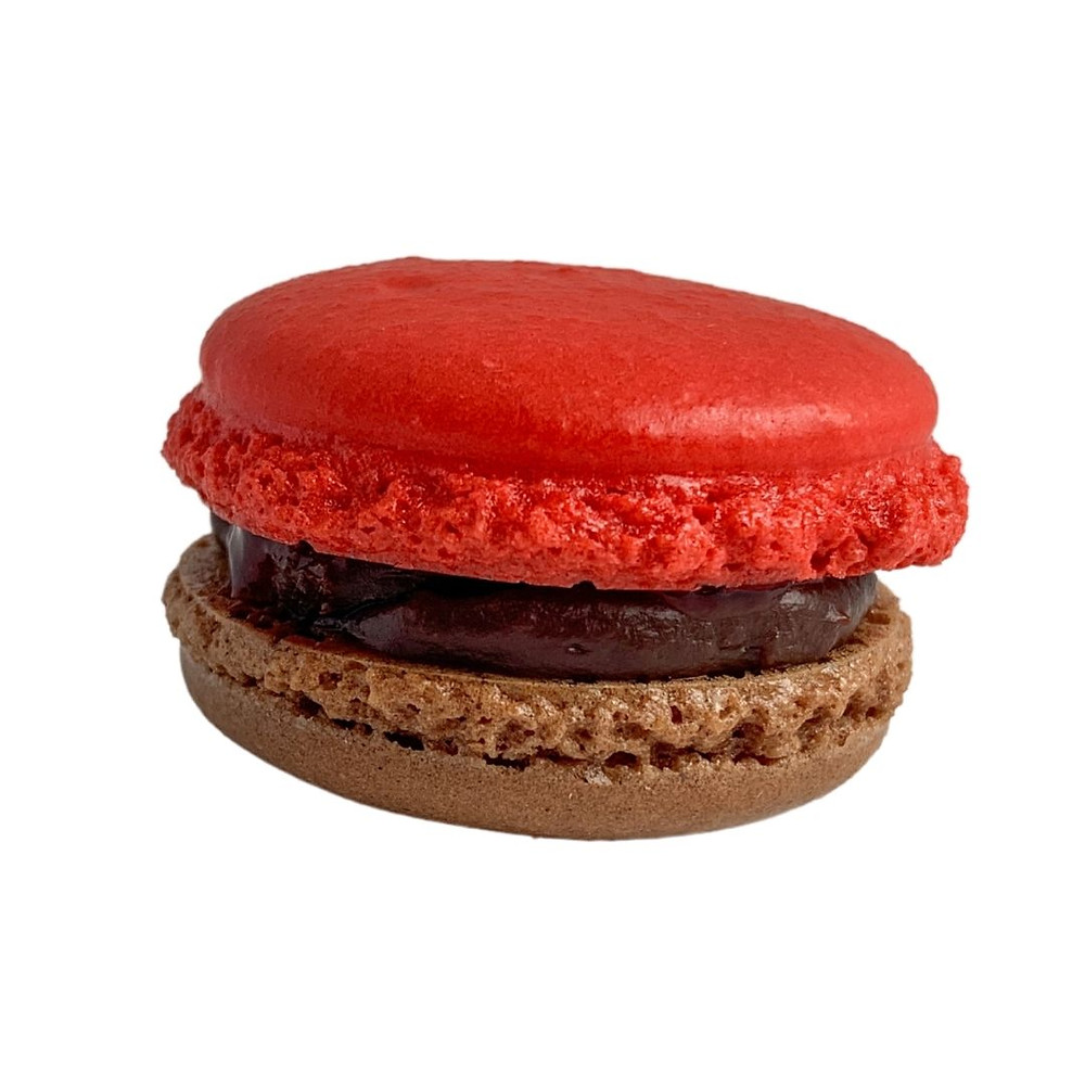 One brown chocolate almond macaron shell and one red almond macaron shell with milk chocolate ganache and sour cherry preserve center.