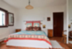Large bed with wooden door to right