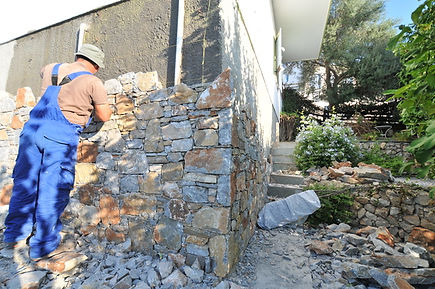 Skilled workman making a stone wall.