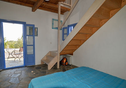 Blue bedcover and french windows opening to courtyard on a Greek island.