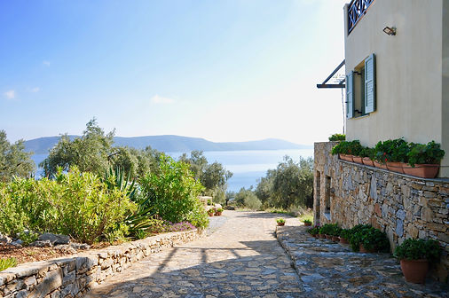 Sone driveway by the side of villa with sea view.