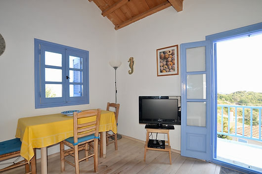 Corner of room with window, french windows to balcony.