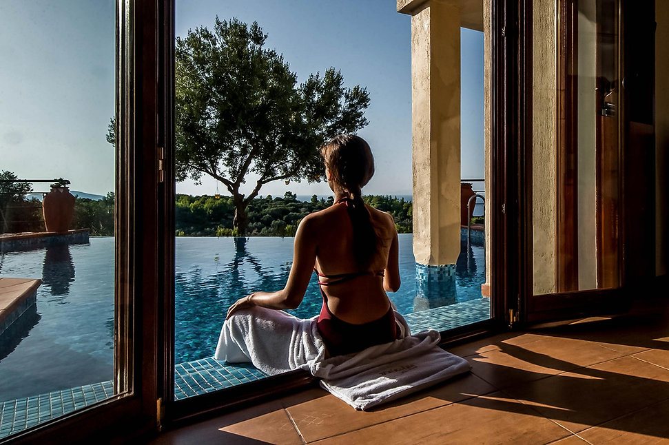 French windows opening out to luxury swimming pool with lady sitting.