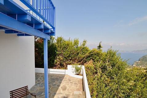 Below blue wooden balcony with sea views in Greece.