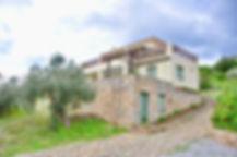 Stone clad Alonissos villa with stone driveway.