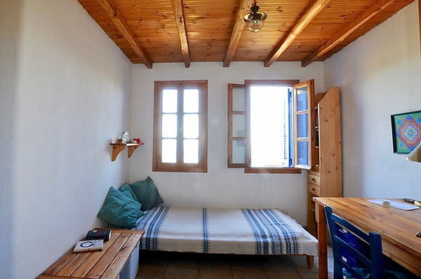 Guest bed with two windows behind