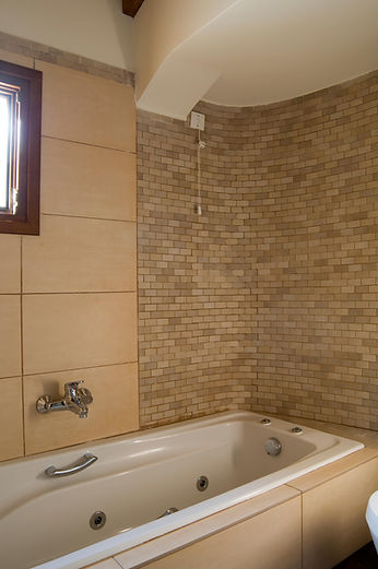 Bath tub with small bricks as tiles on wall.