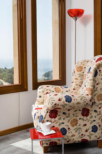 Armchair looking out to two vertical windows.