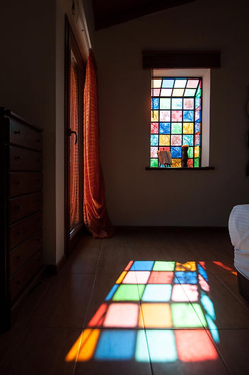Stained glass window casting colourful shadow on wooden floor.