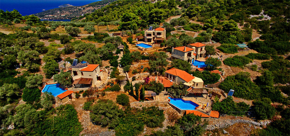 View from above of four luxury villas with swimming pools.