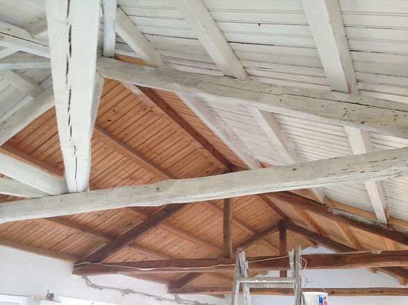 transitional stage of bare wooden ceiling beingpainted white.