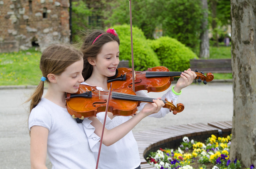two young girls and friends play violin together