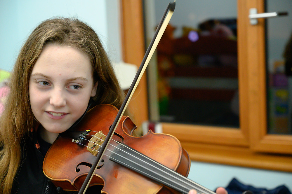 teenage girl practicing the violin