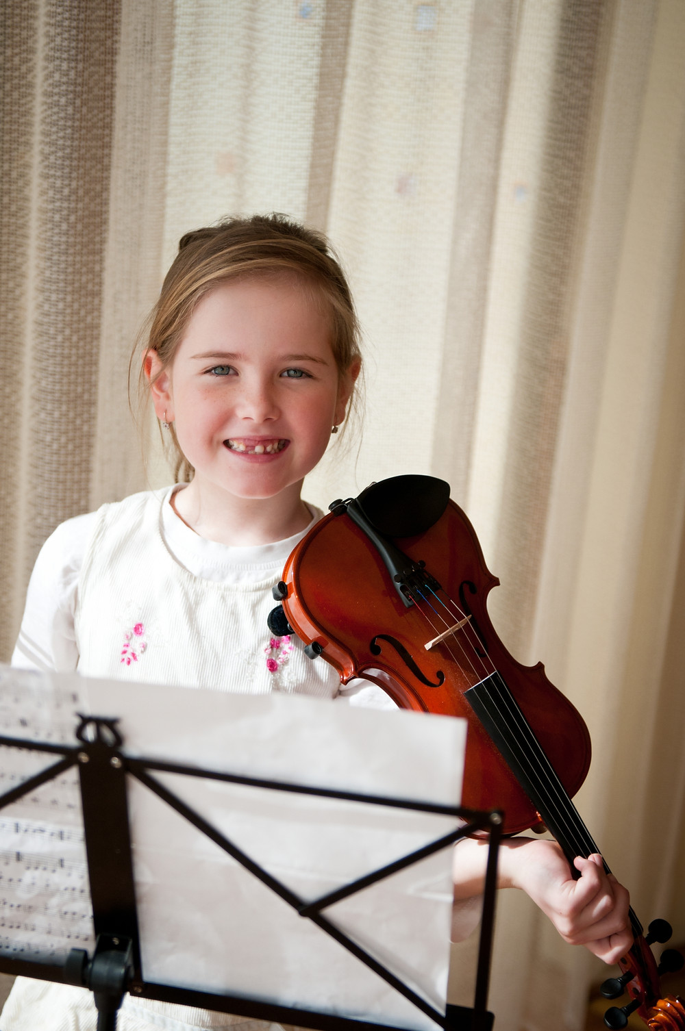 young girl smiling and playing violin