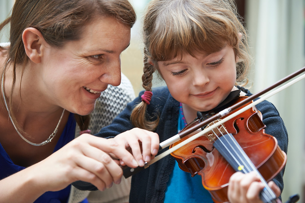 Mother and young girl practicing violin