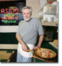 Joe Woytovich, owner taking pizza out of oven