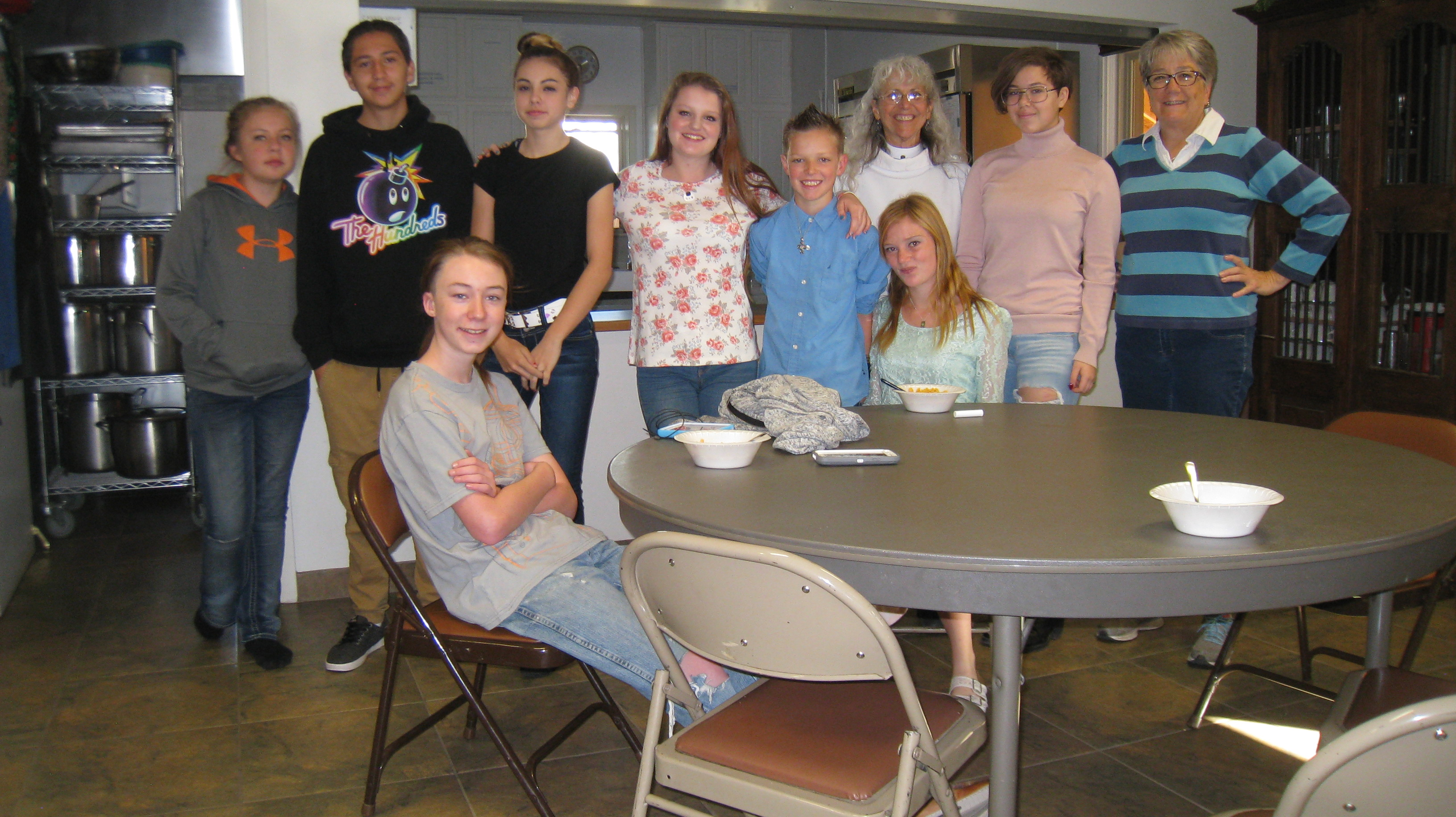 Youth group clustered with priest