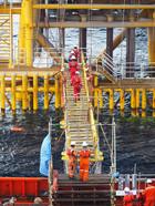 Construction crews cross gang way from a