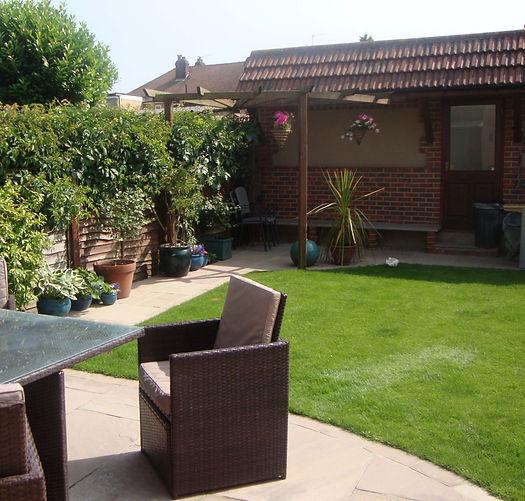 A landscaped garden with premium paving and a brick built garden building/garage.