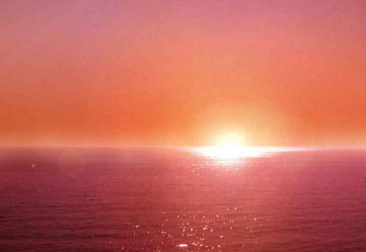 L'océan sur Énora, coucher du soleil orange sur l'horizon