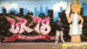 UR-78 artiste graffiti qui pose devant une fresque haute de 4 metres, deco graffiti, tag, design et street art