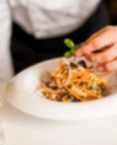 chef garnishinga pasta salad wit basil