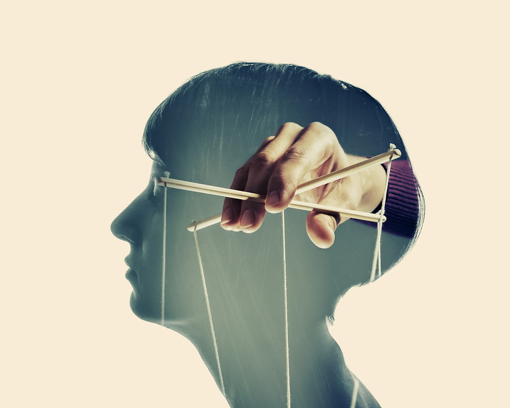 a hand puppeteering inside a human mind