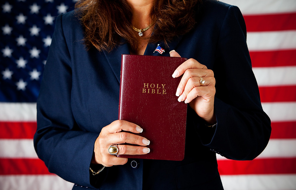 woman holding the bible in front of the american flag representing the lack of separation of church and state in the united states