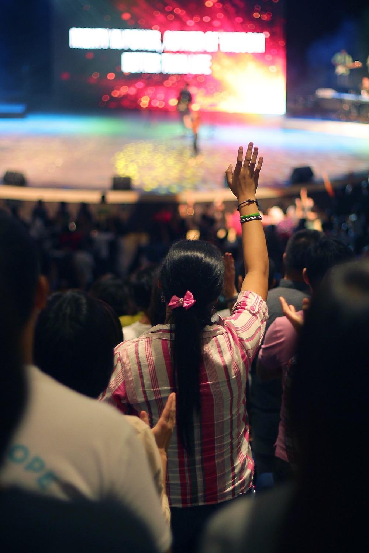 Woman worshiping in a mega church.