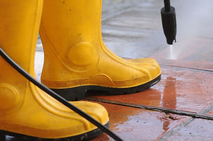 person-wearing-yellow-rubber-boots-with-high-pressure-water-nozzle-cleaning-dirt-tiles.jpg