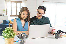 serious-asian-husband-checking-analyzing-statement-utilities-bills-sitting-together-at-hom