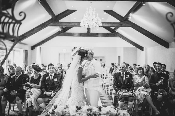 brides kissing at Coed Y Mwstwr