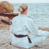 Young attractive karate woman in white k