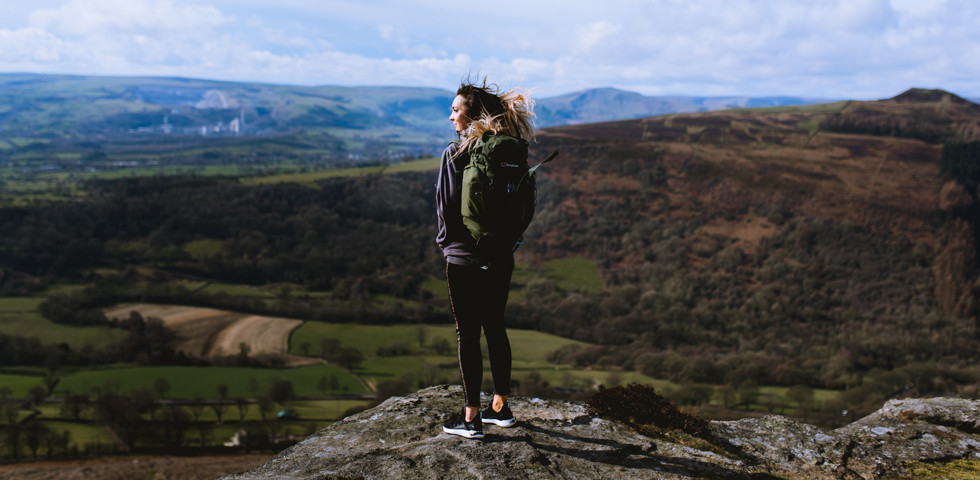 A girl in outdoor clothing looking out over a valley.