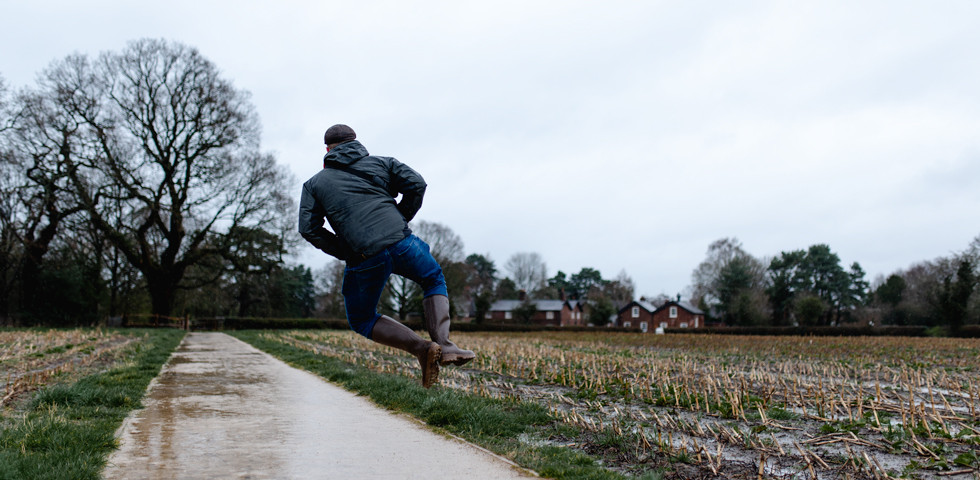 A man jumps with happiness because he's outdoors.