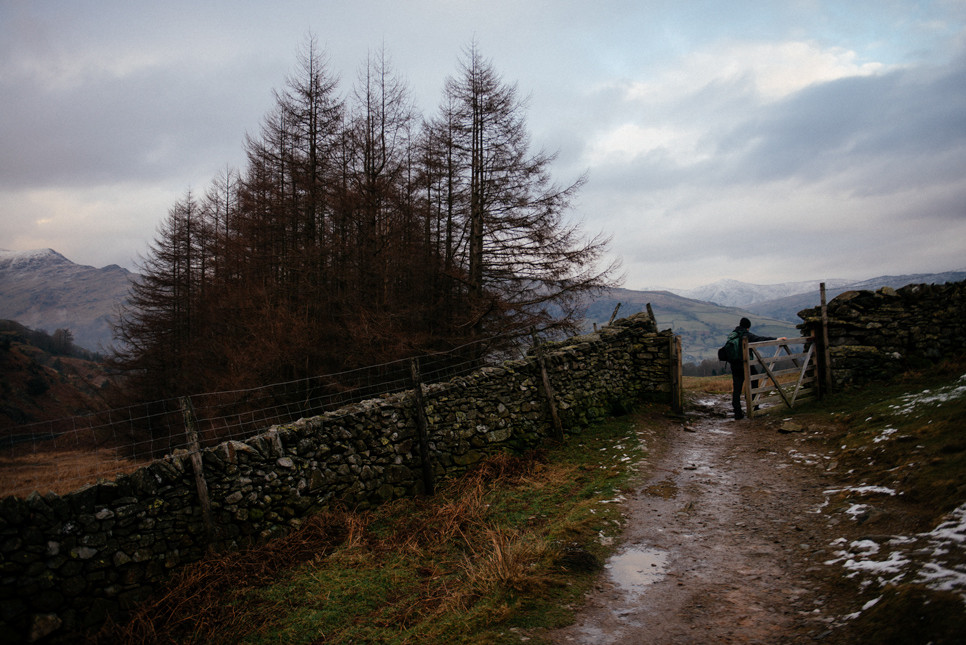 A man walking through a gate in the Lake District