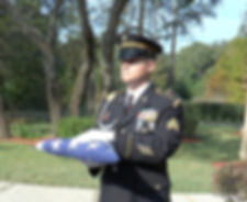 Military Member holding USAFlag at Memorial Service