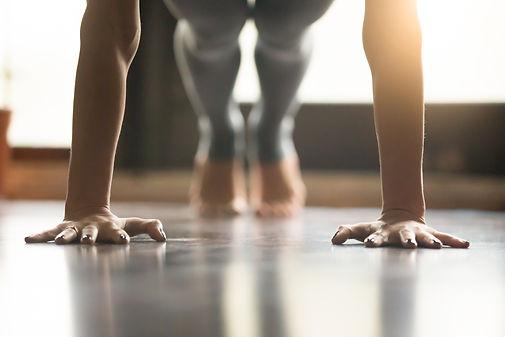 Young woman practicing yoga, doing Push ups or press ups exercise, phalankasana Plank pose