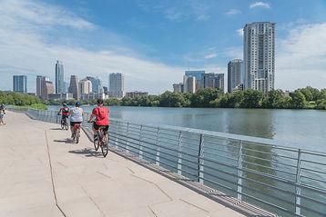 People biking running walking along Colorado River waterfront boardwalk near downtown Aust