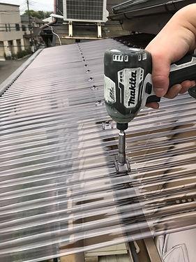 所沢のリフォーム会社原田ホームの社員が台風被害にあったバルコニーの波板の修理をしている。