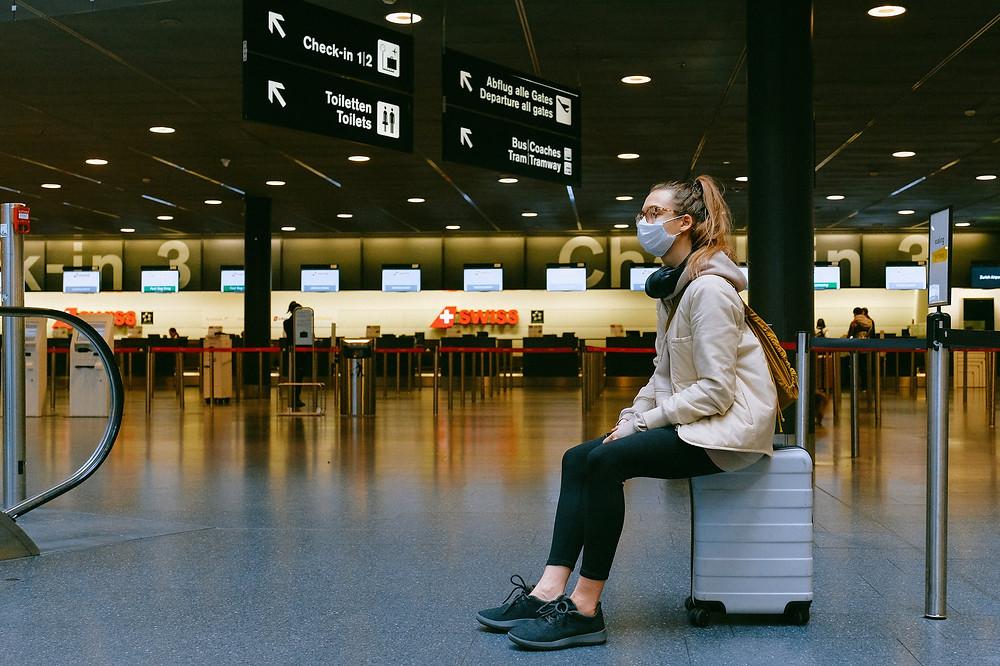 Mulher no aeroporto com uma mala, com uma máscara em tempos de pandemia covid-19
