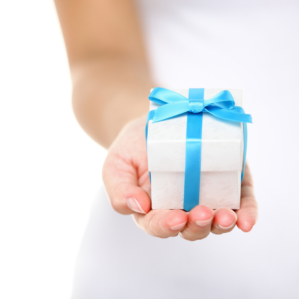 present or christmas gift hand close up. Decorative gift box tied with a turquo
