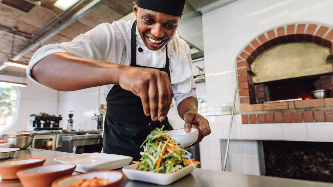 Male chef preparing salad in kitchen. Go