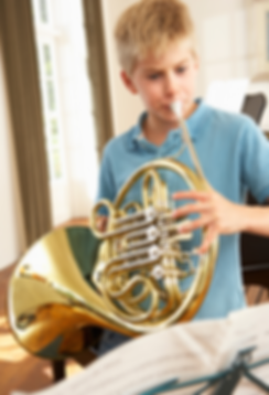 a young man reading music and practicing the French horn in his parent's home