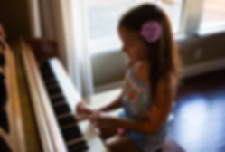 young piano student practicing her scales at home on the family piano