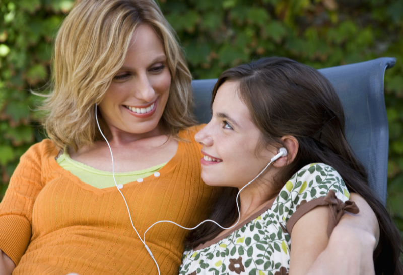 mother and daughter listening to classical music at a normal volume with ear buds