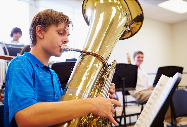 high school music student practicing his scales on the tuba during a break at band practice