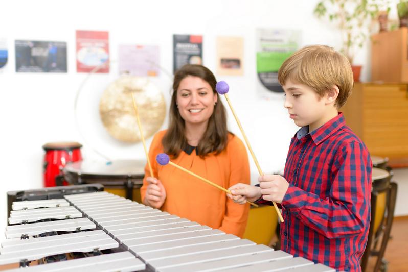 a marimba teacher giving a music lesson at her studio.