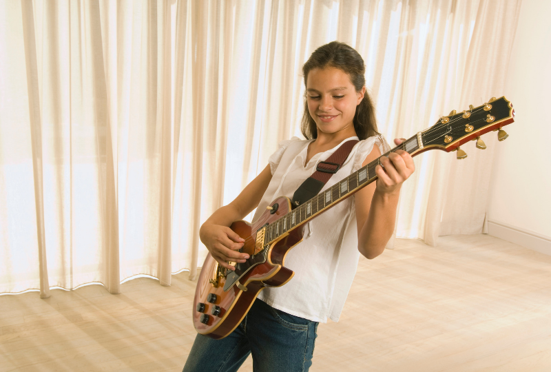 A child practicing electric guitar at home.