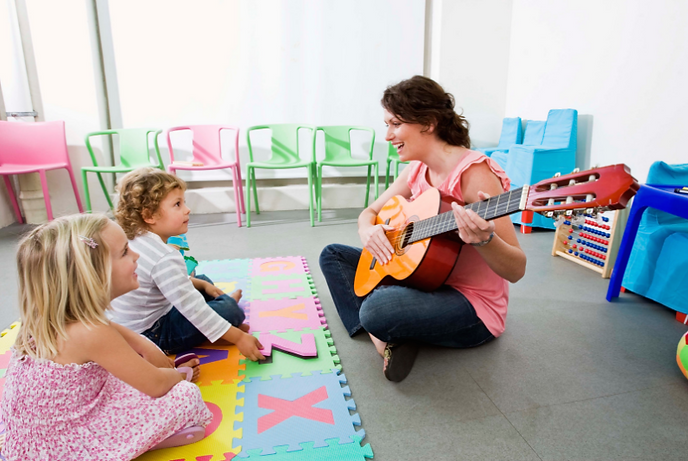 A guitar teacher engaging with her students demonstrating creativity and passion for music education.